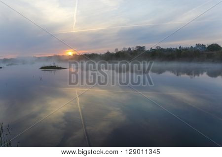 The plane trace in the sky similar to a symbol of a victory is reflected and below in water.