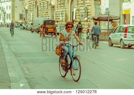 FLORENCE, ITALY - JUNE 12, 2015: Woman ridding bycicle and texting at the same time. Street with a lot of ciclists on Florence.