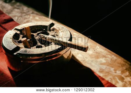 Cigarette on stainless ashtray. on morning light.