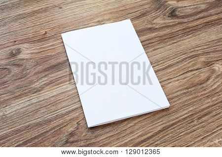 Blank of brochure is on a wooden desk. Template for your design.