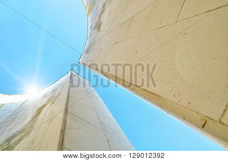 Architecture urban background with perspective bottom view of semicircular walls in futuristic style. Modern architecture cityscape with sunlight at the top.