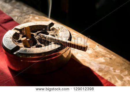 Cigarette On Stainless Ashtray.