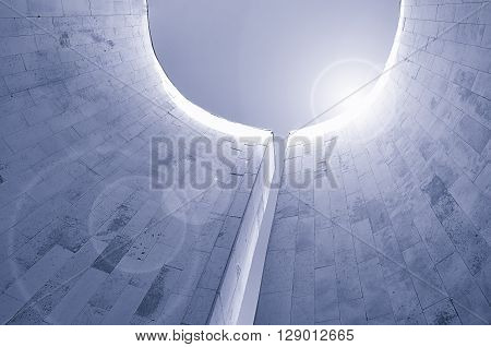 Perspective bottom view of semicircular walls built in futuristic minimalist style. Architecture urban background with reflected lights. Modern architecture cityscape in cold futuristic tones.
