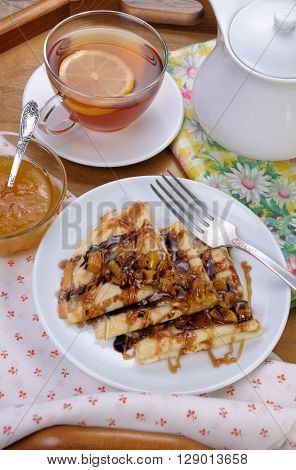 Breakfast pancakes on apples with caramel and chocolate and cup of tea