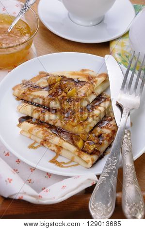 Pancakes sliced apples with caramel and chocolate for breakfast