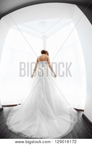 Beautiful young bride in white wedding dress indoors.  Luxuty model standing against big window at home. Girl waiting her groom and prepearing her gorgeous look in bright room. High key, made on fisheye lens photo.
