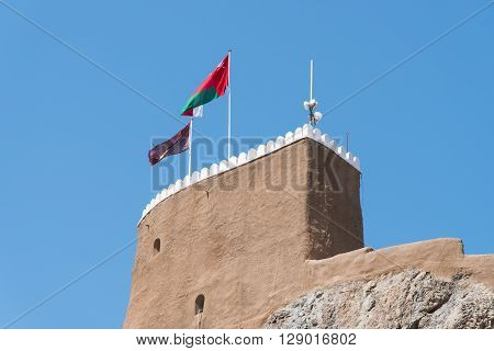 Detail of the medieval Fort Al-Mirani in Muscat The Sultanate of Oman. The Omani flag in the foreground.