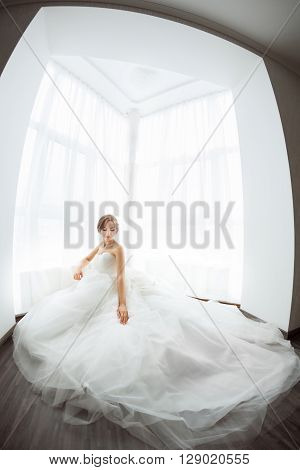 Beautiful young bride in white wedding dress indoors.  Luxuty model sitting against big window at home. Girl waiting her groom in bright room and looking at her gorgeous dress.  Fashion wedding look. High key fisheye photo.