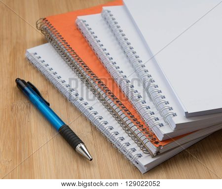 Stack of white and orange Personal office notebooks and a pen
