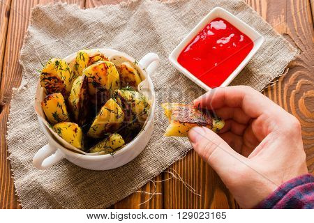 man eating fried potatoes with ketchup wooden background