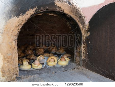 Easter eggs coverd with bread and Cypriot cheese pies cooked on a clay oven.