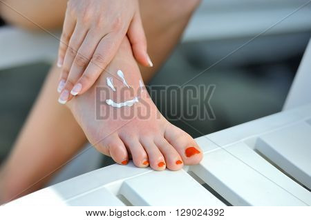 Care for beautiful woman legs. Smile shape on woman feet