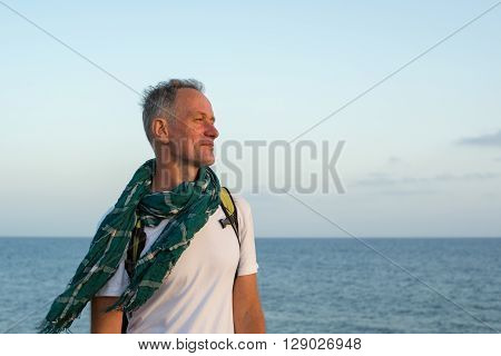 Portrait of a smiling traveler standing on the beach in windy weather.