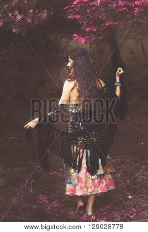 barefoot boho girl in infrared garden full body shot back view