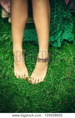 barefoot woman feet on grass with ankle bracelet shot from above