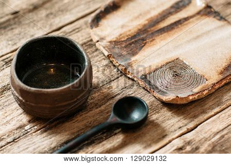 Rustic handmade eco friendly pottery crockery set  on wooden table. Creative brown ceramics with nature pattern. Empty clay plate, wooden spoon and ceramic bowl on old wooden background