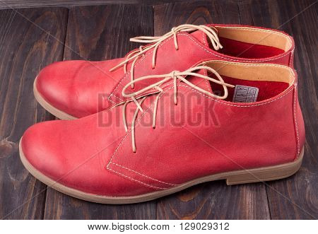 red women's leather shoes with laces on a wooden background.