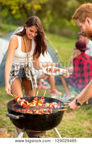 Cute girl and guy together baked barbecue in outing in nature