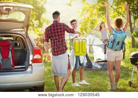 Group of happy friends unpacking car for camping trip