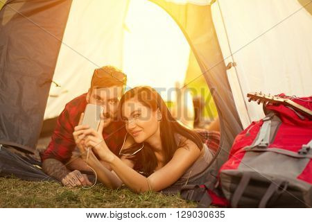 Campers self portrait, woman and man smiling in tent, happy people having fun.