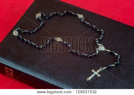 Rosary beads and crucifix on black Bible on red background