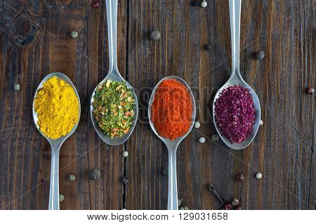 Close up Image of Grey Metal Spoons with Selection of Aromatic Seasonings on Rough Dark Natural Wooden Board Table