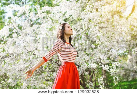 Beautiful Happy Woman Enjoying Smell In A Flowering Spring Garden