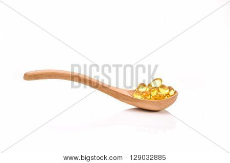 Fish oil capsules in a wood spoon on white background