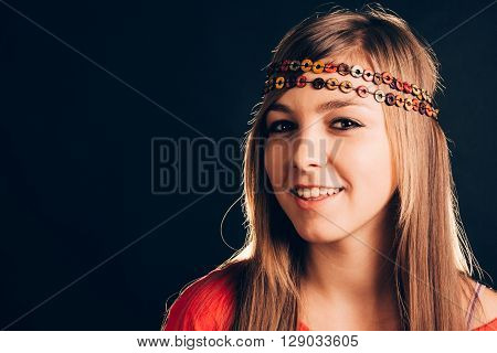 Closeup of a beautiful blonde smiling woman with boho headband - isolated on black.