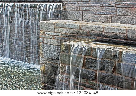 Waterfall from a fountain cascading over brickwork horizontal format.