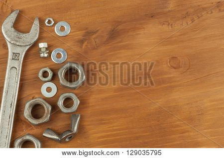 Bolt and nut on a wooden background. Mounting spanner. Background with working tools. Workshop equipment. Buyers repairman.