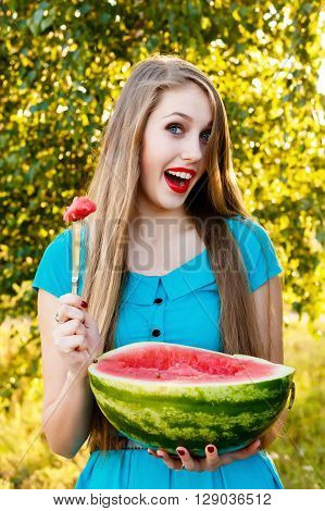 Beautiful blonde girl in a blue dress with long hair eating a watermelon outdoors