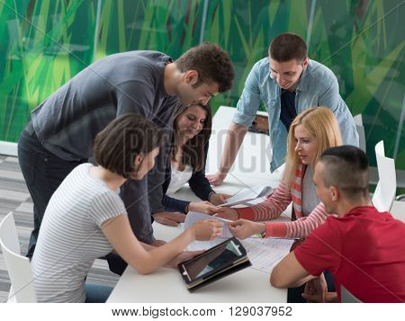 students group study together in school classroom and working together homework project on tablet computer