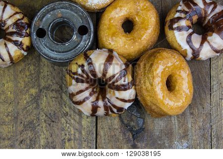 Close up top view of various dougnuts and vintage cutter isolated on rustic wood background