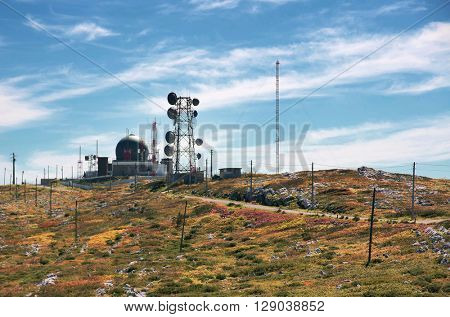 Big wireless communications antennas in a hill under a blue sky