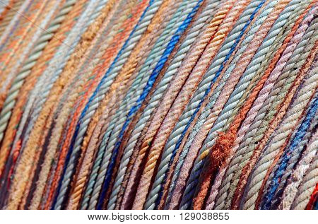 Background of aligned colorful old fishing ropes under sunlight
