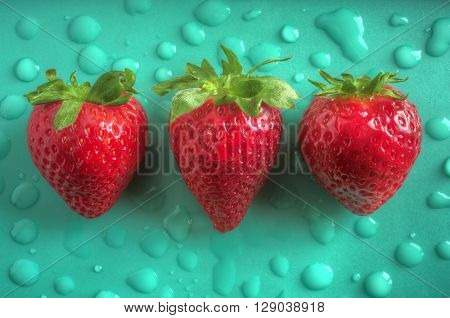 Three aligned strawberries over emerald green background with water drops