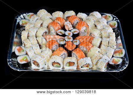 many fresh and tasty sushi rolls on black