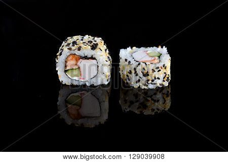 two fresh and tasty sushi rolls on black