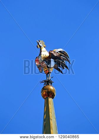 Weathervane in the form of a golden rooster on the spire tall tower