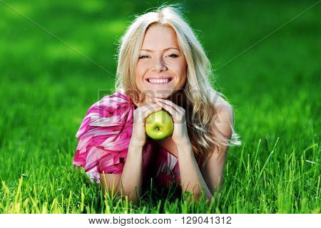 Beautiful young woman with apple lying on green grass