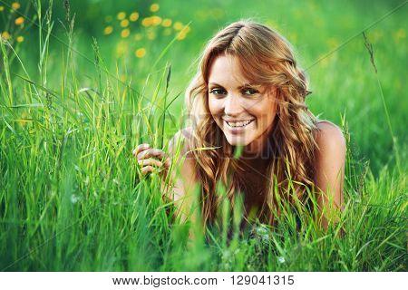 Beautiful young woman outdoors lying on green grass
