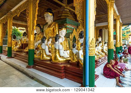 Yangon Myanmar - January 9 2012: Monks and people seated near the Buddha satues in the Swedagon Pagoda.