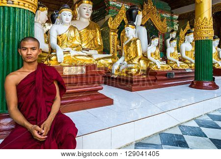Yangon Myanmar - January 9 2012: A monk seated near the Buddha statues in the Swedagon Pagoda.