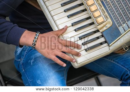 Closeup of musician hand playing on a vintage accordion