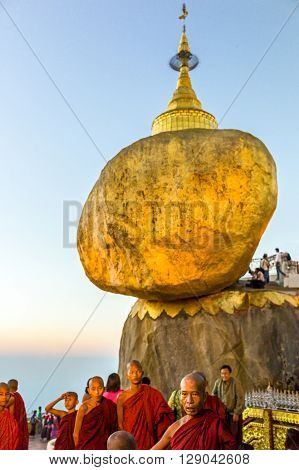 Kyaikhto Myanmar - January 10 2012: Monks under the delicately balanced golden Stupa on the sacred Buddhist mountain