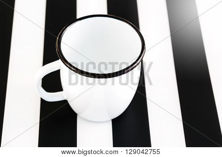 Empty Cup on Black and White Striped Background