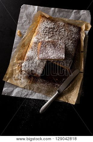 almond cake just baked with powdered sugar on a black stone kitchen table. Northern light effect in a low key