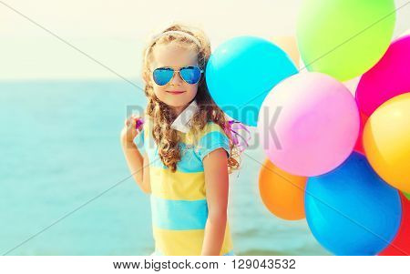 Portrait Of Happy Smiling Child On Summer Beach With Colorful Balloons Over Sea