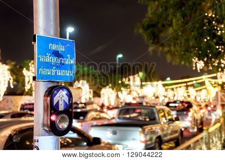 Push button for Red traffic light in Thailand thai language. Translation: push button wait for walk signal. City road at night. Selective focus blurred background.